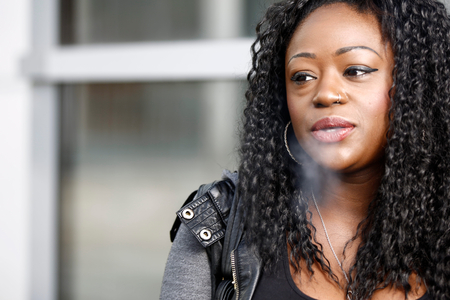 Young African woman smoking a cigarette exhaling smoke through her nostrils with an expression of satisfaction, close up head and shoulders