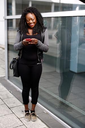 femme africaine: Trendy jeune femme africaine lisant un message texte sur son t�l�phone portable alors qu'elle se trouve sur le trottoir en face d'un immeuble urbain
