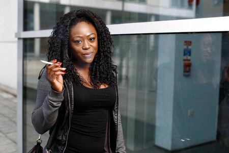 femme africaine: Sourire attrayant femme africaine avec une belle coiffure debout boucl�s fumer une cigarette dans une rue urbaine avec un sourire sur son visage