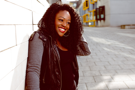 Happy Attractive Black Woman in Black and Gray Jacket Fashion, Leaning at the Wall while Touching her Curly Hair.