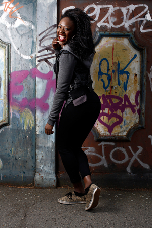 high spirited: Happy African American Woman in Casual Fashion Outfit Posing at Wall with Vandals While Looking at Camera.