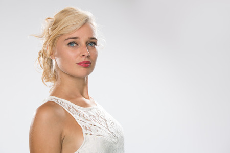 Woman looking to camera with blonde hair and wearing a white dress Foto de archivo