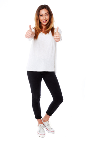 Happy young woman giving a double thumbs up gesture to show her enthusiasm and motivation or the fact that she has been successful full body on white Foto de archivo