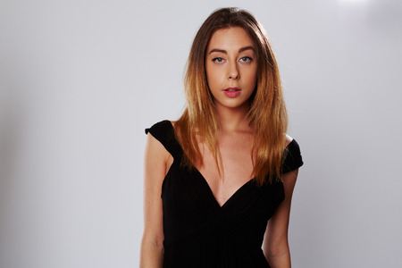 Attractive young woman in a stylish black dress and her long blond hair loose on her shoulders, looking at the camera with a serious expression