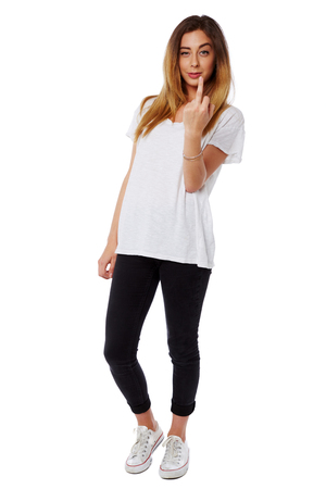 Casual young woman giving a rude gesture by raising her middle finger at the camera with a snigger and look of glee, full body isolated on white