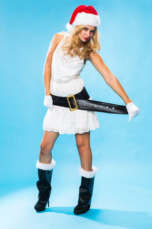 Cute sexy blond woman in a Santa hat and costume celebrating Christmas pulling on the broad black belt to emphasise her shapely figure over a turquoise background