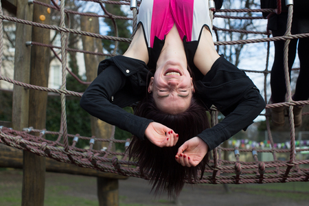 Young Woman Hanging Upside Down and Laughing on Outdoor Climbing Rope Jungle Gym Foto de archivo