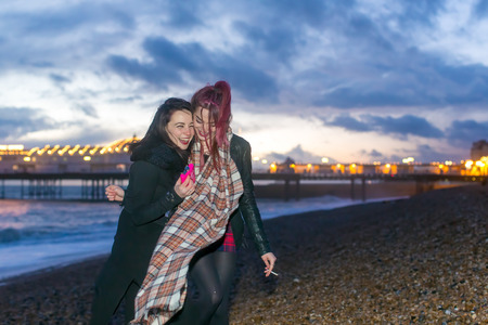 Young couple of lesbian girls enjoying a night out at the seaside laughing and smiling as they hug each other on the beach with city lights in the background