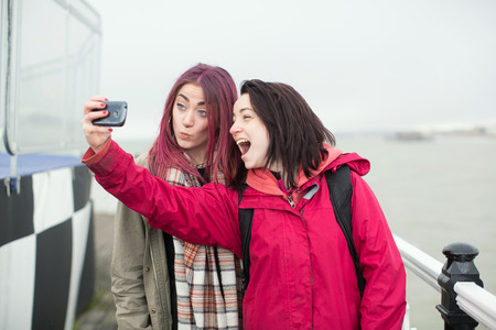 pulling faces: Two playful young women posing for a selfie on a walkway laughing and pulling faces at the camera on their mobile phone