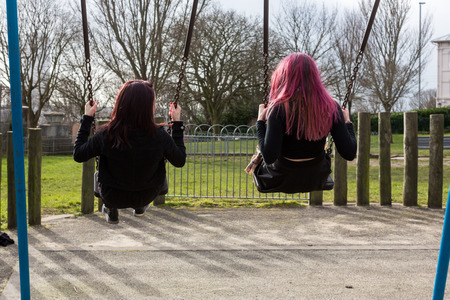 Rear View of Two Young Funky Women Swinging on Swings at Playground in Spring Time