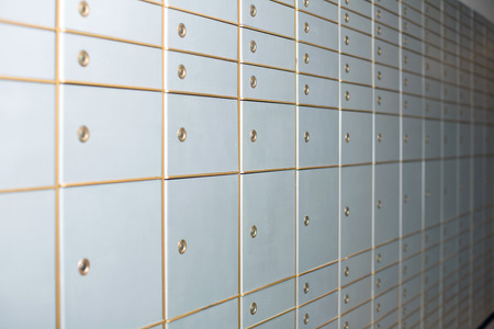 White closed multiple lockers of various sizes with golden borders and secured with locks mounted on an interior wall closeup from oblique angle