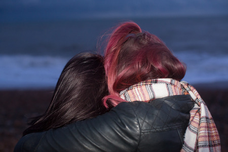 Close Up of Two Women Hugging with Arms Around Each Other Rear View on Beach at Dusk One with Pink Hair 스톡 콘텐츠