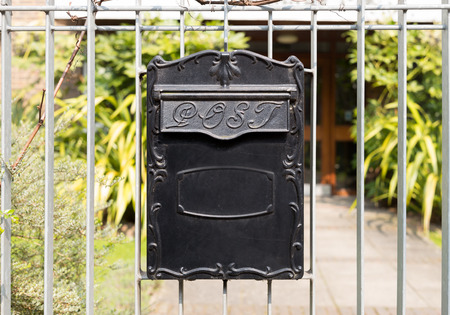 Close up Black Metal Post Box in Vintage Style Hanging on Railings or Gate of a House.