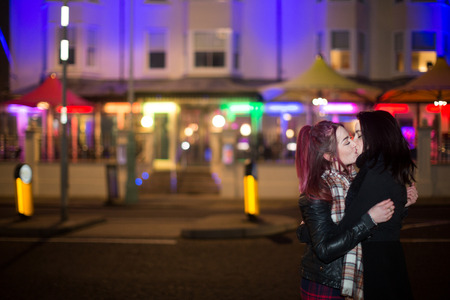 Female Same Sex Couple in Love Kissing Outdoors at Night in Urban Setting