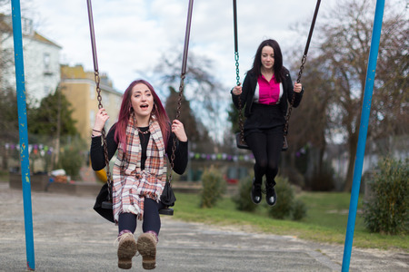 Front View of Two Young Funky Women Swinging on Swings and Chatting at Outdoor Playground