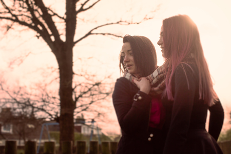 Two Teenage Girls Standing Together Outside at Sunset in Warm Light with Sun in Background