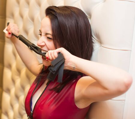 dominatrix: Close up Happy Pretty Young Woman in Sexy Red Shirt Biting a Leather Whip While Leaning on the Wall.