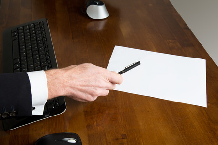 Hand of a businessman wearing black formal suit with white shirt while holding a pen over a black computer keyboard and a blank paper sheet placed on a wooden desk in the office, close-up