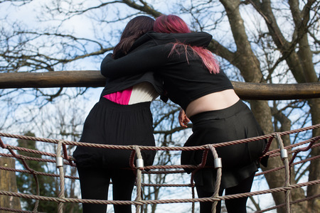 Rear View of Two Young Funky Women Hugging on Outdoor Playground