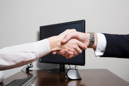 Handshake of two equal associates, sign of mutual agreement, over the wooden desk of a business office with modern equipment as desktop PC with keyboard and web camera
