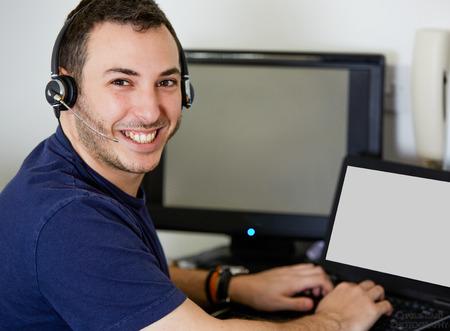 computer center: Close up Hermoso Call Center Agent individuo sonríe en la cámara mientras trabajaba en su ordenador portátil.