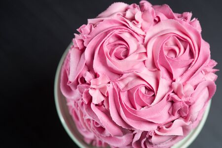 Overhead view of a freshly baked cake decorated with pink icing sugar roses displayed on a cake stand over a black background with copyspace