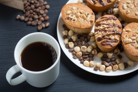 White cup of coffe and cookies in a white plate
