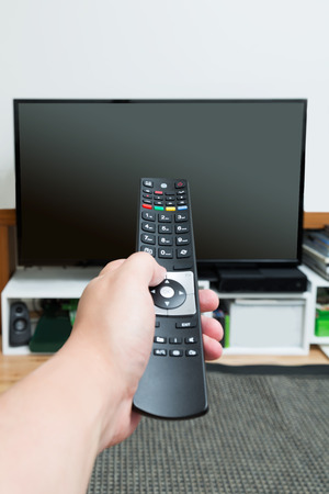 Close up of hand holding and pointing remote control at turned off flat screen television