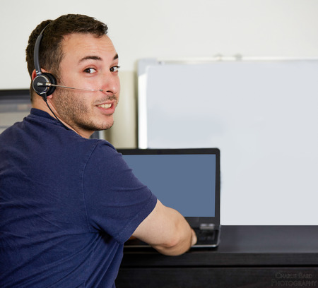 Young Handsome Man with Headset, Looking at the Camera From his Back While Working on his Laptop Computer at the Table.