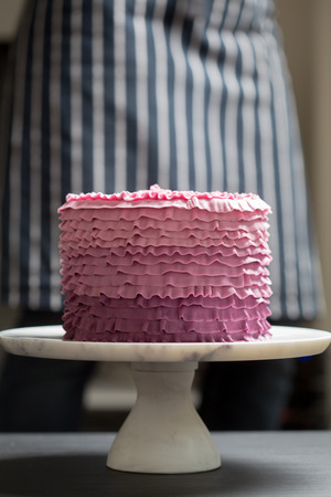 Handmade pink cake on a white stand