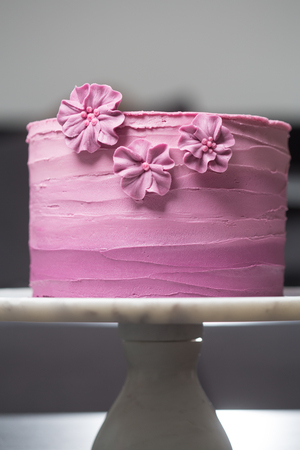 Pink cake decorated with pink flowers on a stand 스톡 콘텐츠