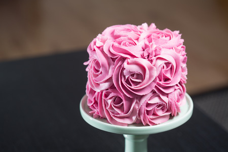 Gourmet cake for a wedding or birthday decorated with pink icing sugar roses covering the surface displayed on a stand over a black background with copyspace