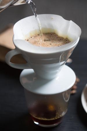 papel filtro: Preparación del café en un filtro manual de verter agua hirviendo sobre los granos de café recién molido, vista de cerca de la superficie del agua y espumosa del café