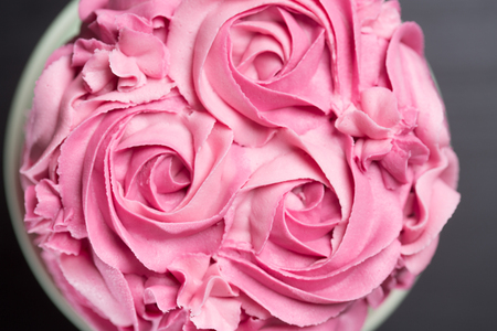Pretty pink cake decorated with handmade icing sugar roses for a special occasion or romantic celebration viewed from the top over a black background