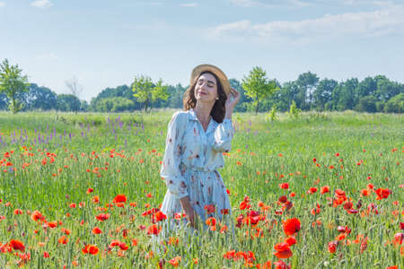 Young woman in light blue dress and a straw hat standing in the red poppies field with closed eyes Banque d'images