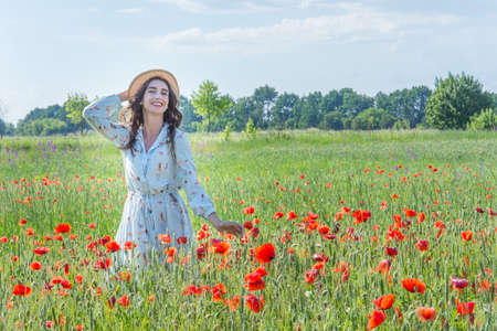 Young woman in light blue dress and a straw hat smiling in the red poppies field
