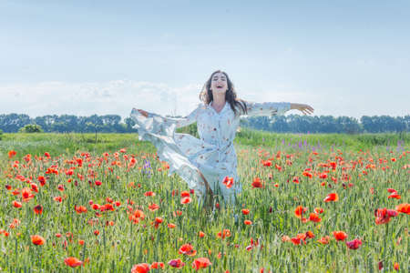 Young woman in light blue dress running through red poppies field