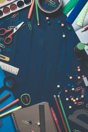 assortment of school stationery such as paper clips, pins,notebook, pens, pencils, rulers, scissors lying on blue wooden table with space to write your ad text Фото со стока