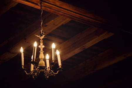 Dimly burning antique chandelier in an attic with wooden beams Banco de Imagens