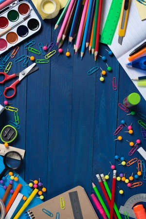 photo on top of various school stationery products such as paper clips, pins, notebooks, pens, pencils, rulers, scissors lying on blue wooden table with space to write your ad text
