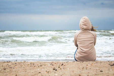 young woman sitting alone on the shore of the stormy sea in cold weather and finding reflects the tranquility and peace of pleasure
