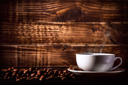 background hot coffee drink in a cup with steam feeded for breakfast with coffee beans on wooden texture