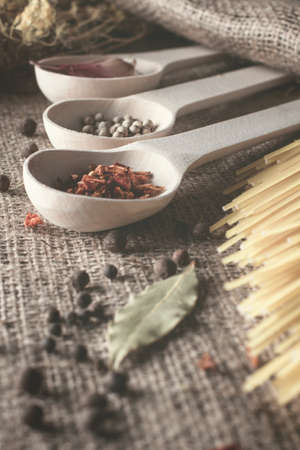 wooden spoons lie in a row with spices for cooking: red peppers, white and black pepper peas, garlic, bay leaf, dill and spaghetti