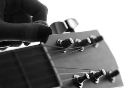 black and white silhouette of a female hand tune a stringed musical instrument - a guitar