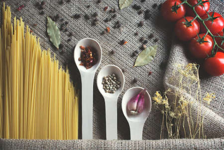 composition of the food on sackcloth: Spaghetti, cherry tomatoes, dried dill, spices in a wooden kitchen spoons: bell pepper, garlic, white pepper, Stok Fotoğraf