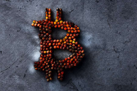 Burnt bitcoin sign on a metal texture, the concept of a crypto currency crash