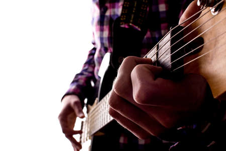 Hands of a young guy on strings playing electric guitar on white isolated background