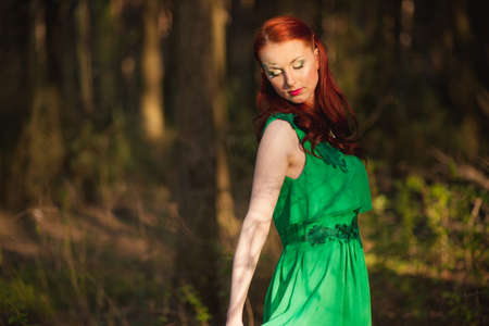 cute lady: Beautiful red hair fairytale girl in green dress with face art Stock Photo