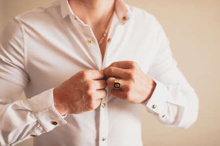 warm shirt: A man buttoning his shirt with his hands