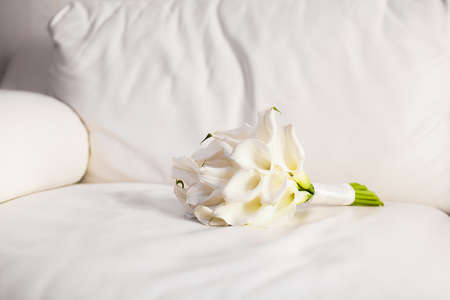 white sofa: Beautiful bouquet of white lily on the white leather sofa